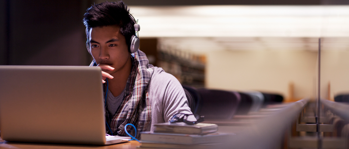 College student studying at library on laptop with headphones