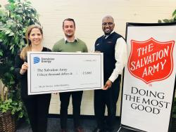 Dominion Energy and The Salvation Army holding grant check.