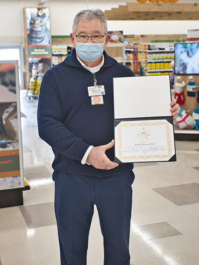 John Spaulding poses proudly in the pets department of his store holding his Fred Meijer Award certificate.