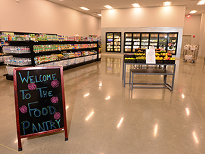"A brightly lit food pantry with well-organized and fully-stocked shelves with a sign that says ""welcome to the food pantry"" in colored chalk"