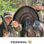Girl holding a Federal shot shell posing with with a harvested turkey and another hunter.