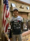 Pro shooter KC Eusebio holding two trophies.