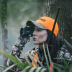 Hunter in blaze orange using a Bushnell rangefinder