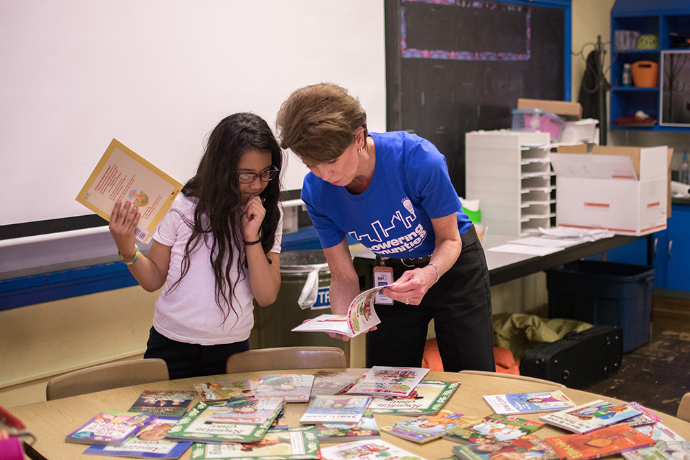 A student at Cleveland Elementary School in Allentown, Pa., carefully selects her summer reading books from a PPL volunteer.