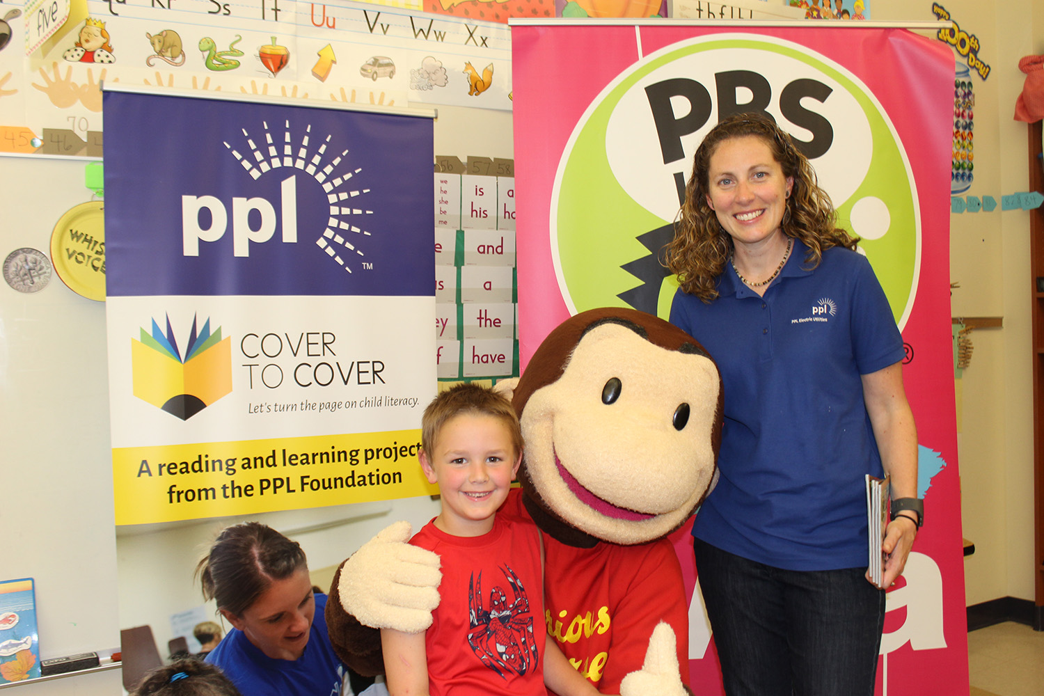 PPL Regional Affairs Director Alana Roberts poses with a youngster at Stourbridge Primary Center in Honesdale, Pa. PPL partnered with WVIA to bring the Cover to Cover program to Stourbridge.