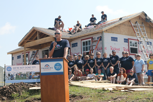 Man speaking at podium with new home construction and Farmers team members behind him