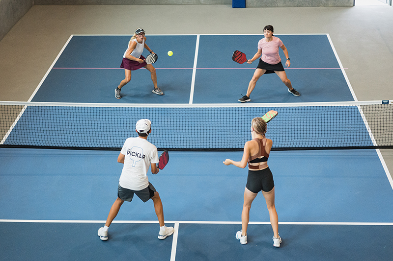 Four Adults playing pickleball