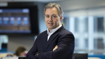Felipe Facchini, Head de Vendas do PayPal Brasil, de terno cinza e braços cruzados, tendo ao fundo o escritório do PayPal