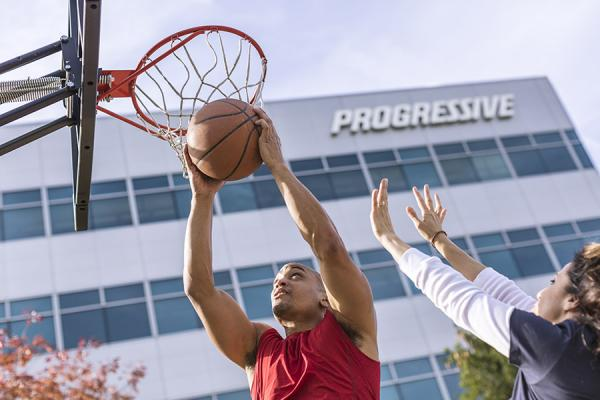 Man and woman playing basketball outside of Progressive building