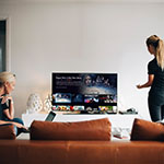 Two women viewing SLING TV's user interface on a television in a living room