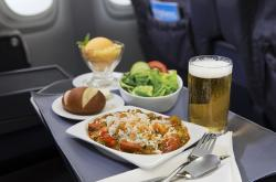 Plate of chicken and sausage jambalaya with dinner roll, glass of beer, and cup of sorbet, served on airplane tray table.