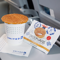 Stroopwafel sitting on cup of illy coffee on a plane seat's tray table.