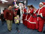 Little boy passenger greeted by a giant snowman and Mr. and Mrs. Claus