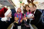2 smiling little girls get hugs from 2 United flight attendants during a Fantasy Flight