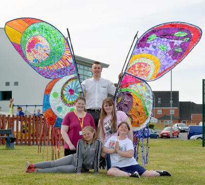 WPD Planner Mark Mears, is pictured with volunteers and members of the Sparkle youth club and craft group from the Serennu Centre, with their butterfly banner.